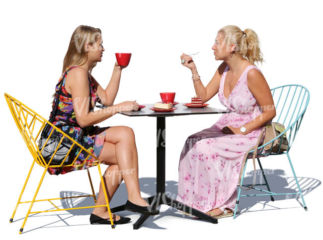two women sitting in a cafe and eating cake
