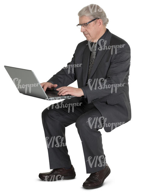 older businessman sitting at the desk and working with laptop