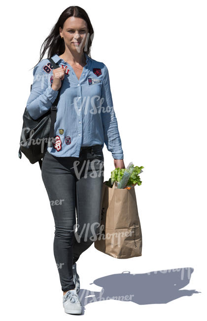 woman with a bag of groceries walking