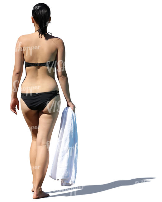 woman in a black bikini walking with a towel in her hand