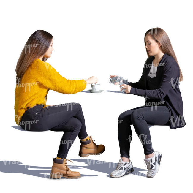 two teenage girls sitting in a cafe
