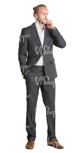 young man in a suit standing and talking on a phone