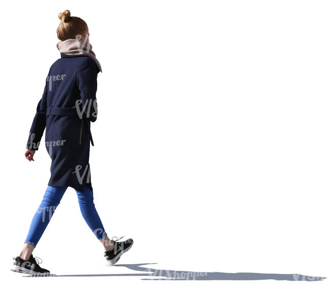backlit young woman walking down the street
