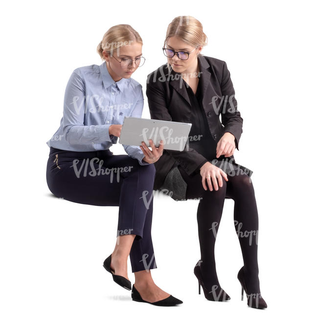 two businesswomen sitting and looking at some papers