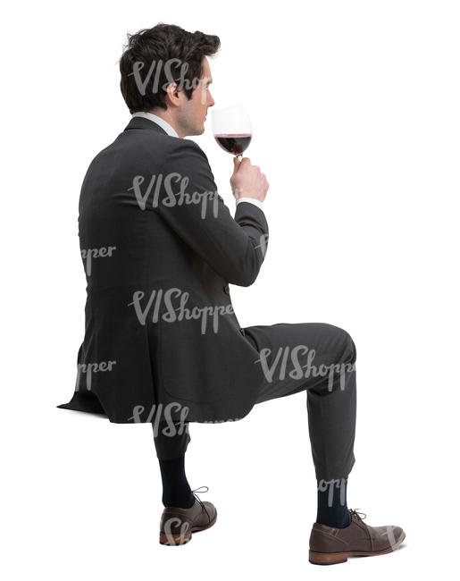 man in a suit sitting and drinking wine