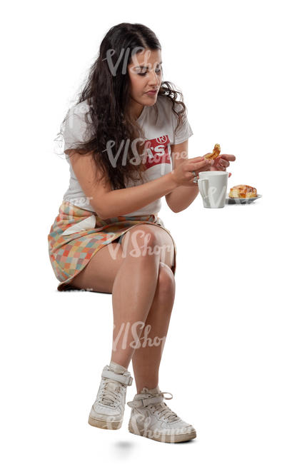 woman eating a bun in a cafe