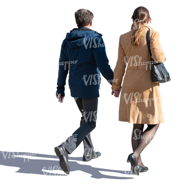 backlit man and woman walking hand in hand