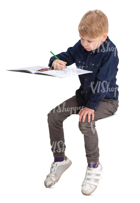 boy sitting behind the desk and drawing