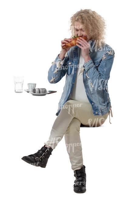 woman sittng in a cafe and eating a sandwich