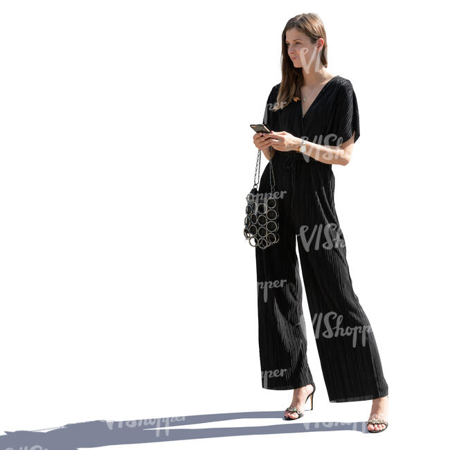 backlit woman in a black jumpsuit standing