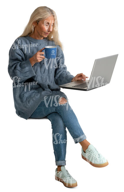 senior woman drinking coffee and looking at laptop