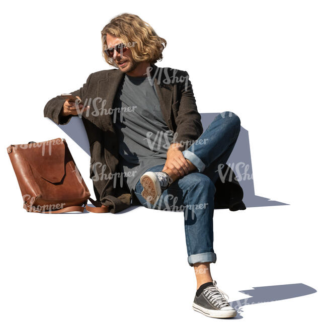 man sitting on a bench and checking his phone