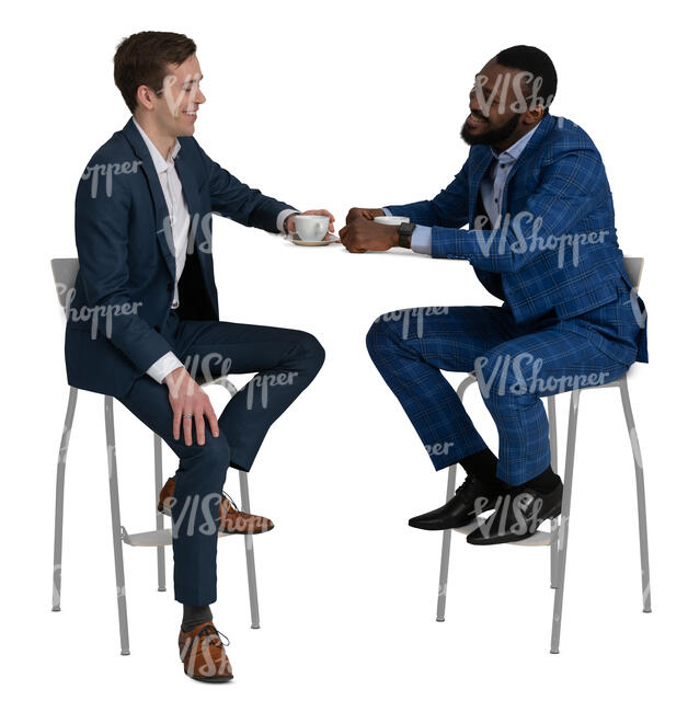 two men in suits sitting in a cafe and talking