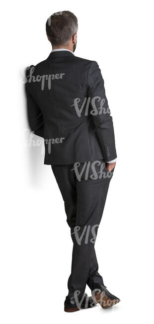 man in a suit standing and leaning against the wall