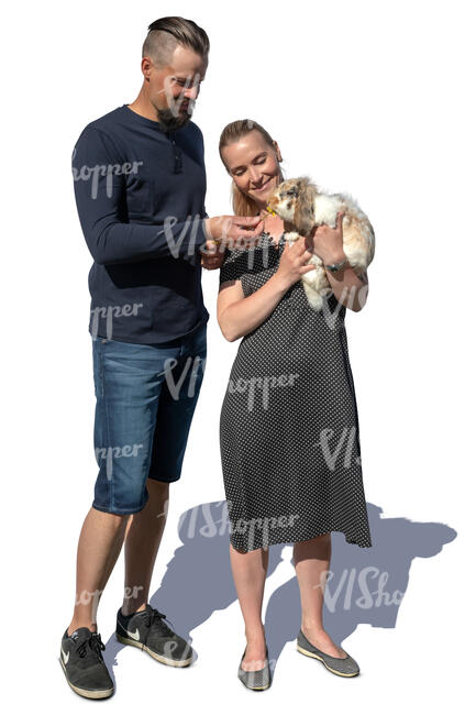 man and woman standing and feeding a rabbit
