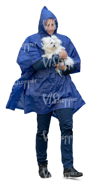 man wearing a blue hooded rain jacket walking and  carrying a small dog