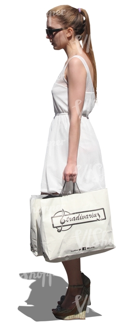 woman in a white dress and with a big shopping bag