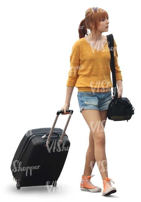 woman in shorts pulling a suitcase