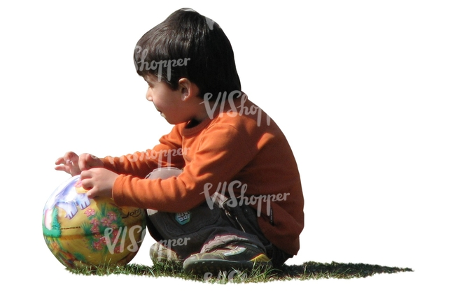 boy with a ball squatting on the grass