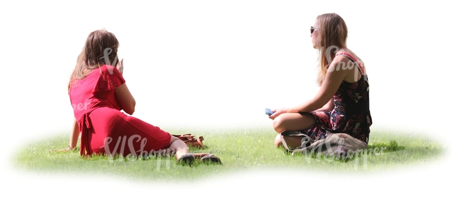 two women sitting together on the grass
