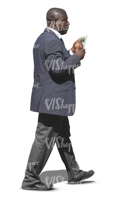 black businessman walking and looking at his tablet