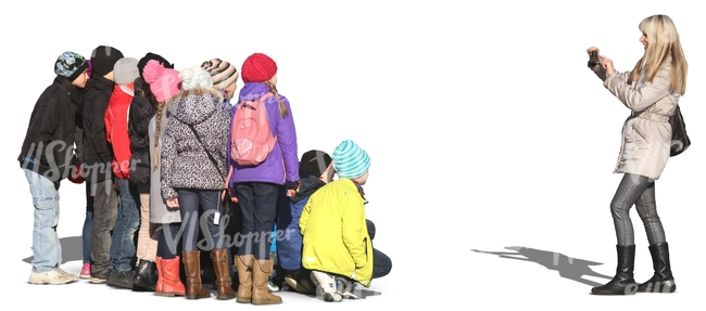 woman taking a picture of a group of children