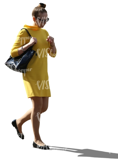 cut out backlit woman in a yellow dress walking