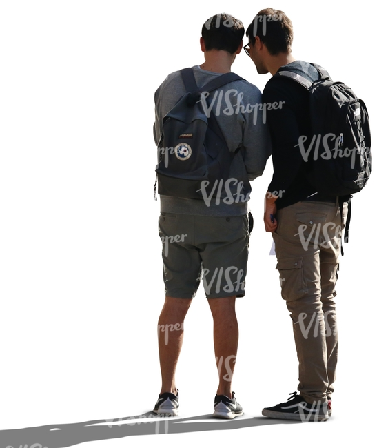 two backlit men standing and looking at smth