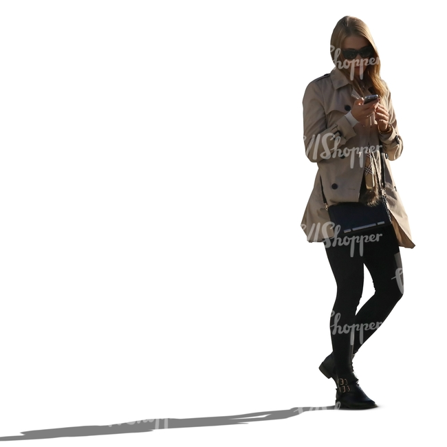 backlit woman in a trenchcoat walking phone in hand