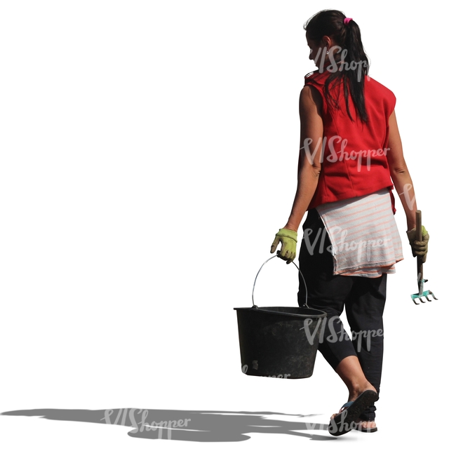 woman with a rake and a bucket walking