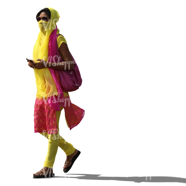 young hindu woman in a clorful outfit and holding a phone walking