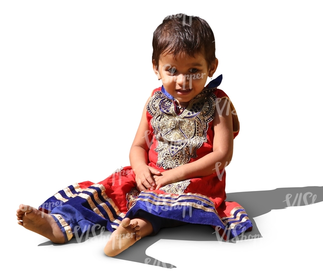 little hindu girl in a fancy dress sitting no the ground