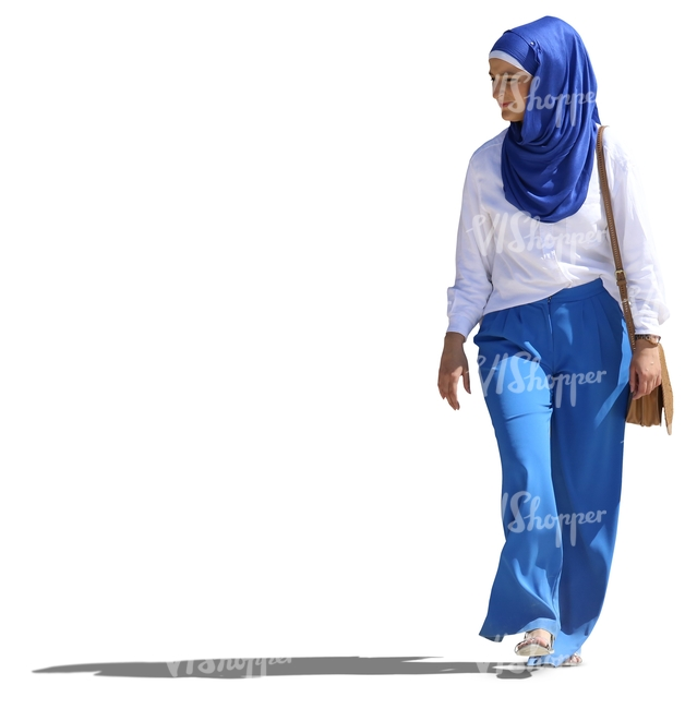 young muslim woman in a blue and white outfit walking