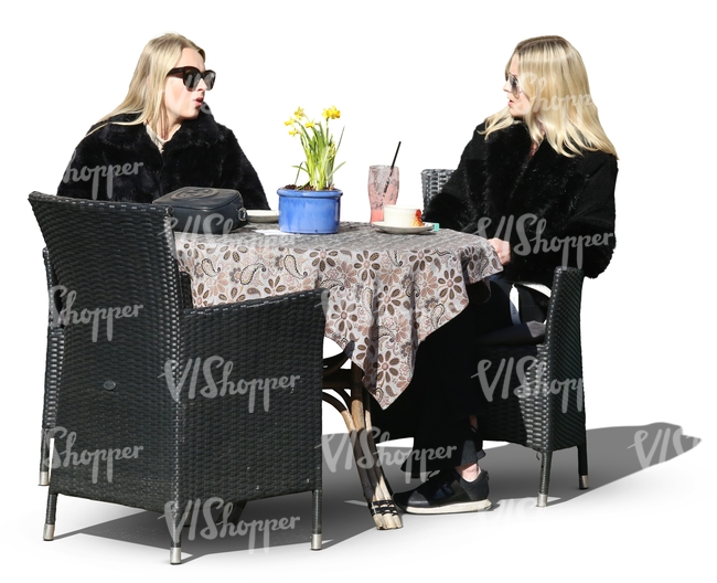 two blonde women sitting in a street cafe and talking