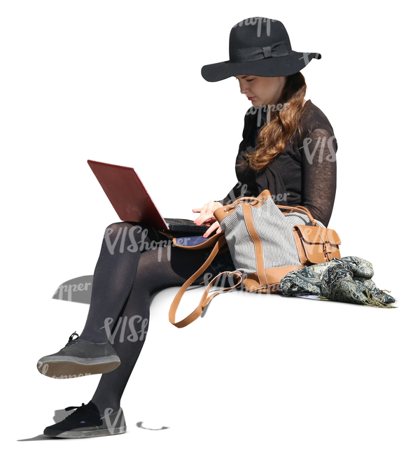 woman with a large hat sitting and working with a laptop.