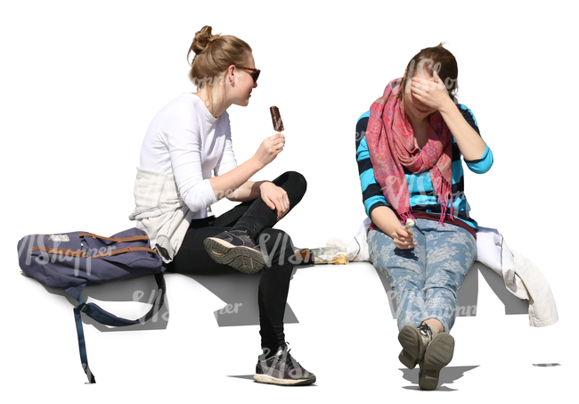 two young women sitting and eating ice cream