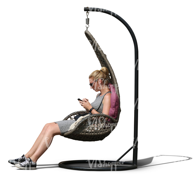 woman sitting in a hanging chair and looking at her phone