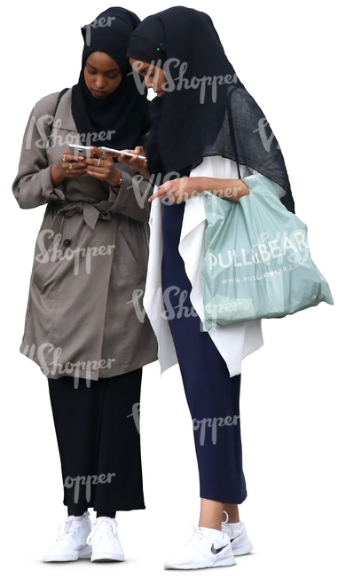 two young muslim women standing and looking at their phones