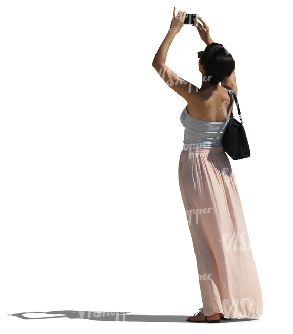 woman in a long skirt taking a picture with her phone