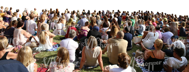 big group of people sitting on a grass on an outdoor event
