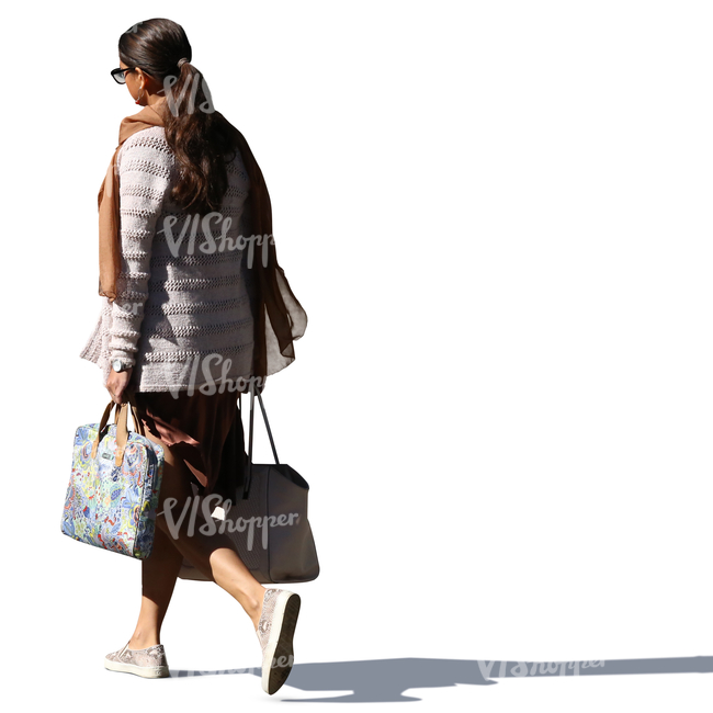 backlit woman walking and carrying two bags