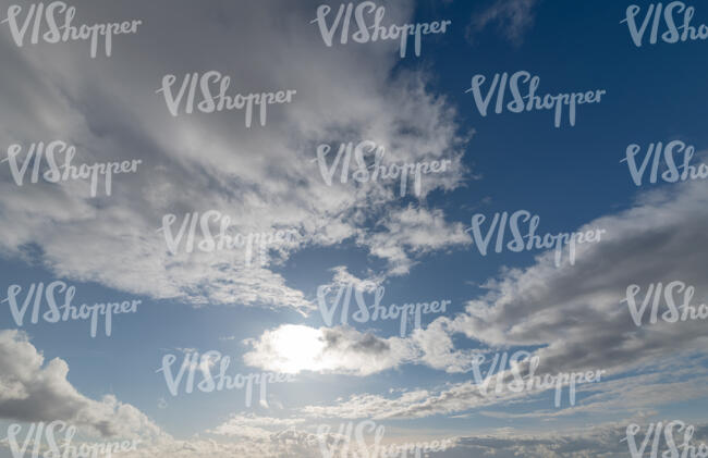 daytime sky with sun behind a small cloud